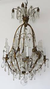 impressive chandelier with antique finish gilt bronze gilt corona supporting crystal prisms and four fine bronze