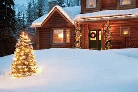 lit christmas tree in front of log home decorated with lights and christmas decorations anchorage southcentral alaska digitally altered