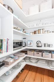Beautiful walk-in pantry fitted with stacked floating wraparound shelves  filled with kitchen accessories, a collection of spices, microwave and  cookbooks.
