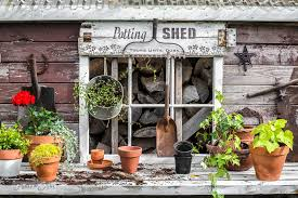 potting shed sign with an old rake that holds garden tools on a rustic garden shed