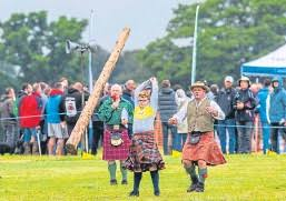 CBBC's Yasmin Evans tries her hand at tossing the caber at Blairgowrie and  Rattray Highland Games. Fellow presenter Ed Petrie looks on. - PressReader