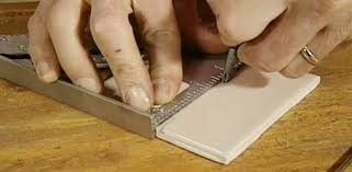 scoring ceramic tile with a glass cutter to cut the tile to size