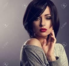美しい化粧ボブ ショートヘア スタイルと赤い口紅の暗い影の背景にポーズ