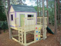 a raised playhouse with a slide and climbing wall