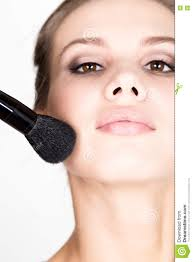 close up female model applying makeup on her face beautiful young woman applying foundation