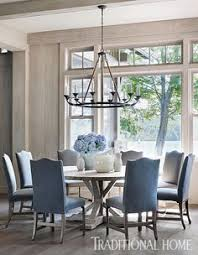 a lola chandelier from bungalow clic hangs above the round elm dining table