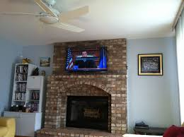tv installation over a brick fireplace with wires concealed in wire molding