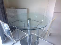 round glass table and 4 clear plastic chairs