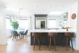 blue kitchen peninsula with curved wood counter stools