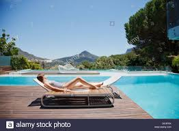 woman sunbathing on lounge chair next to luxury swimming pool with mountain view