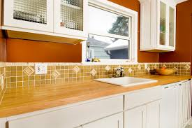 butchers block countertop on white kitchen cabinet with u shaped tile backsplash