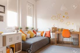 Orange Bedroom Furniture Yellow And Orange Accessories In Modern Teen Room Stock Photo