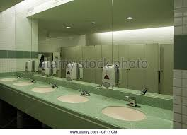 public bathroom mirror. Public Washroom With Several Sinks And Bathroom Stalls Visible In Mirror - Stock Image O