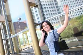 a business woman waving goodbye at an office building home office early