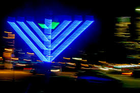 an illuminated menorah blurred by moving the camera during a time exposure in front