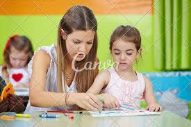 Nursery Teacher Nursery Teacher Helping Girl Painting In Kindergarten Photos By Canva