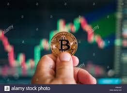 Hand Holding A Gold Coin Bitcoin On The Background Of The
