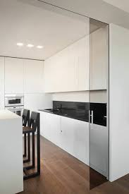 minimalist white kitchen separated with dark glass sliding doors