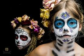 two s with sugar skull makeup on one with blue and the other with red make