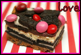 oreo cheesecake bars on a chocolate chip cookie crust topped with a chocolate glaze raspberry m m ore oreos