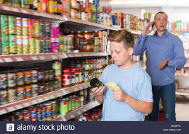 Grocery Store Product List Serious Preteen Boy Choosing Food Products On Shopping List In