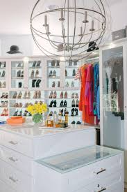 Hats flank a small square window positioned above built-in white glass  front shoe cabinets fixed over shoe shelves located adjacent to open built  in ...