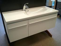 interior white solid wood floating cabinet with marble top and single trough sink also stainless steel