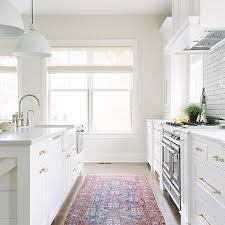 white kitchen with rustic wood ceiling beams and red and blue kilim rug