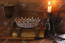low key image of beautiful diamond queen crown on old book burning candle vine
