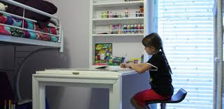 child coloring at wall mounted folding desk