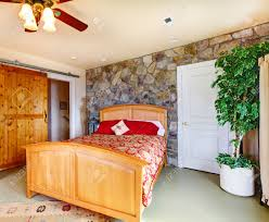 Exotic Bedroom Interior With Stone Wall Trim, Wooden Bed And Decorative  Tree In Corner Stock
