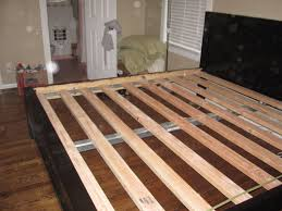 homemade king size bed frame with black rustic finish and white wooden slat bed on laminated floor