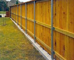 steel supports in concrete support a wooden fence lining a playground