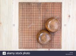 Game With Stones And Wooden Board top view two wooden bowls filled black and white stones over empty 96