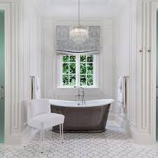 tiered crystal chandelier over tub flanked br frosted glass his and hers showers