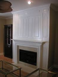 hide a flat screen tv behind millwork paneling over the fireplace love how this