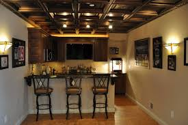 basements with wooden hanging bar cabinet and white bar table in glossy countertop facing black iron barstools in cream leather pads over laminate floor