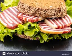 Sandwich Of Black Bread With Sausage And Salad Close Up Stock Photo