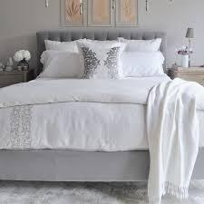bedroom gray tufted headboard white throw blanket linen bedding