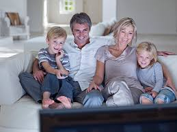 family watching tv at night. watching tv winter is on the way and one to keep family together out of cold cozy couch with a good movie. at night