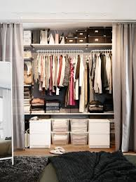 Create a floor-to-ceiling closet by attaching rods and shelves to a wall,  then draping off the area with a set of curtains.