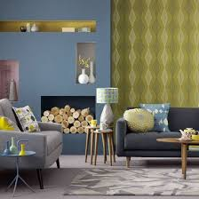 blue and yellow living room graphic wallpaper teamed with soft blue paint and geometric prints creates bold living room furniture