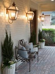 outdoor front porch with metal bench and wall sconces