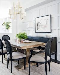 in the dining room a rough hewn farm table paired with clic chairs achieves