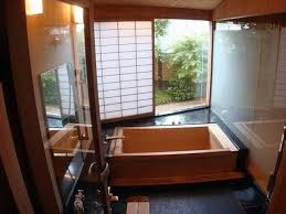 Small bathroom design with a socking bathtub and a sliding exterior door in  Japanese style