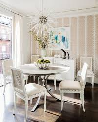 a visual comfort quincy chandelier illuminates white and tan square back dining chairs placed around a round gray dining table positioned in front of
