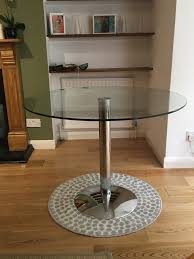 round dining table with a clear glass topin notting hill london ing a dining