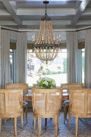 a wood beads chandelier hangs from a gray coffered ceiling above an antique dining table surrounded by wood and mesh dining chairs positioned in front of