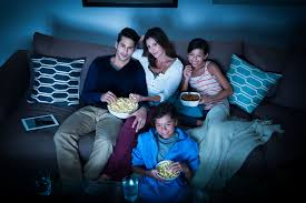 family watching tv at night. have a chilled out saturday night with your favorite actor on screen, friend beside you and of course, ice-cream right in front family watching tv at