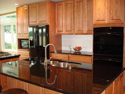 natural wood kitchen cabinet and kitchen island with black counter top also double bowl kitchen sink